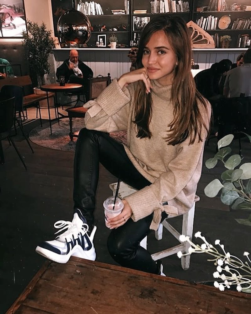 White Ugly Sneakers With Beige Sweater And Black Leather Slim Pants For Fall 2019